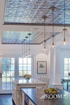 A hand-stamped tin ceiling defines the dual islands in this Nantucket style kitchen in Evanston, Illinois.
