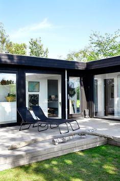Rundt hytta er det bygget en terrasse som flukter med gulvet innendørs, noe som skaper glidende overganger mellom inne og ute.