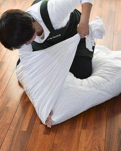 布団をひざで押さえ、シーツの間に手を差し込んで、しっかりと折り目をつけながら左右のシーツを引っぱります。