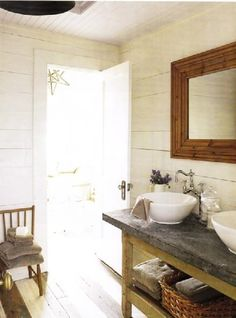 Rustic bathroom with white washed paneled walls! rustic bathroom design with off-white cream paint wall color. Rustic beveled wood mirror, double sinks, round vessel sinks, chrome faucets, wood floors, antique small chair and rustic antique reclaimed wood console table with shelf. Love the Pottery Barn star light pendant as well! off-white cream brown gray purple bathroom colors.