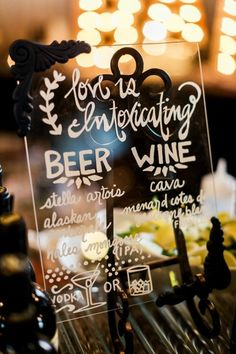 """Clever cocktail hour sign idea - glass sign """"Love is intoxicating"""" with white modern calligraphy + nature motif  {Luma Weddings}"""