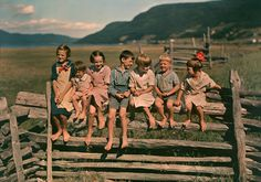 Seven siblings sit on a wooden fence in Quebec, Canada, 1938