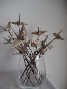 paper cranes put on sticks ~ did this for the extra cranes at the wedding and put them in the centerpieces and beer bottles. Also use them for decoration around the house.