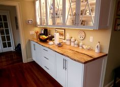 Live edge maple countertop in a country home atop white cabinets.