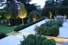 Formal structural 650mq garden on the outskirts of London, where clients asked designer Charlotte Rowe for structured formal planting without too many 'flowers'.    Here an upper terrace of buff-coloured English limestone with a long water feature cutting through surrounded with 'cloud' planting of clipped Buxus sempervirens.     © CharlotteRoweGardenDesign