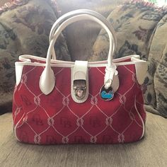 """Dooney & Burke Anniversary Rope Purse Love the contrast of the cream trim on this bright red purse by D & B!! Wonderful, gently used condition. Measures 12""""W x 7""""H, 12""""H with handles. No shoulder strap. Interior is fully lined and includes key leash, zippered center pocket, zippered pocket on back wall and three pockets on front wall. Mild age discoloration on interior bottom and minor wear on handles, everything should clean up beautifully but doesn't detract and I've pictured close up…"""