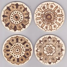 Set of four wooden coasters with pyrography designs based on Persian carpets. Created by Georgina Barnes.