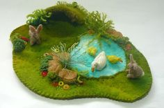 Another miniature felt scene reminiscent of an English rural field with rabbits and a pond.the pond has a mother duck and her two babies. Th...