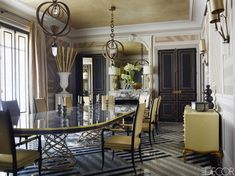 The dining room table and chairs are custom made, and the light fixtures are by Hervé Van der Straeten; striped wallpaper by Osborne & Little and flooring of Carrara and Nero Marquina marble were installed in custom patterns.