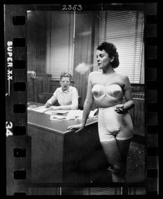 Woman model, standing in an office, smoking while modeling undergarments