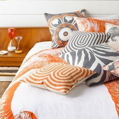 Bedroom - white walls, warm wood, orange and white comforter with orange, grey, and white throw pillows