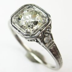 The Airy Cushion: This ring is the perfect balance of crisply linear platinum filigree and a plump and sparkling diamond. Details of the mounting remind us a bit of peacock feathers, with a fan of arches in the under gallery. Ca. 1915. Maloys.com