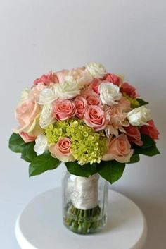 A sweet bride's bouquet filled with green hydrangea, peach roses, peach sprays roses, and white lisianthus.