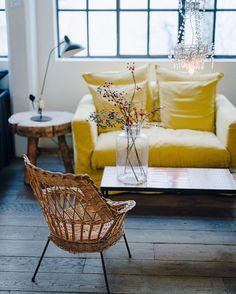 Fauteuil rotin et canapé jaune citron dans le salon