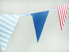 garland of paper flags out of triangles of scrapbook paper in red, white and blue patterns like dots and stripes and a length of grosgrain ribbon.