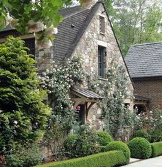 The  beautiful English-inspired stone cottage style home pictured below is of relatively recent origin.   Located near   Atlanta, Georgia, USA, landscape architect Richard Anderson further enhanced the look and feel with a cot-tage garden   that includes a profusion  of  climbing  roses  clinging  to  the stone facade and cascading over the covered entry way.