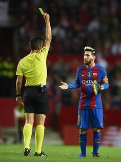 Referee shows yellow card to Lionel Messi of FC Barcelona during the match between Sevilla FC vs FC Barcelona as part of La Liga at Ramon Sanchez Pizjuan Stadium on November 6, 2016 in Seville, Spain.