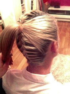 French Braid in back and on top with hair pulled back on the sides into a ponytail