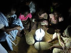 Children and elders gathering around a light source created by the village.