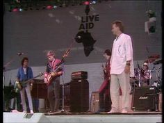 Dire Straits & Sting ☮ Money For Nothing -- July 13, 1985 - At 12:01pm Status Quo started the 'Live Aid' extravaganza, held between Wembley Stadium, London and The JFK Stadium, Philadelphia. The cream of the world's biggest rock stars took part in the worldwide event, raising over 40million pounds. TV pictures beamed to over 1.5bn people in 160 countries made it the biggest live broadcast ever known.