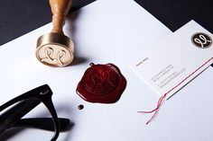 "wow. heavy cards with textured ""hand"", thread woven through card, logo wax seal in blood/royal/passion red."