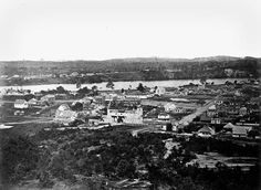 This view of Brisbane in 1862 shows the area around the old Women's Factory Prison. The prison is the building behind the partly completed Normal School. Brisbane's present GPO building was erected near the site of the prison. On the right of the prison is St Stephen's Church, still standing. Edward Street can be seen running down the hill. Queen and Adelaide Streets can also be clearly seen.