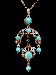 This is not contemporary - image from a gallery of vintage and/or antique objects. JESSIE M. KING (1875-1949) LIBERTY & Co.  An Arts & Crafts gold pendant set with cabochon turquoise within a border of blue enamelled leaves and with a turquoise drops.