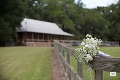 A beautiful country elegant bridal bouquet of all white with the farmhouse in the backdrop..  One of my favorite images from Frank Carnaggio photography in Birmingham AL