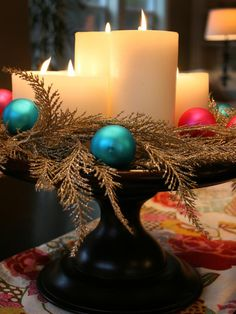 Warm and Festive    Update an existing candle tray to warm up your holiday dining experience. Janell Beals wrapped glittery garland around neutral everyday candles and scattered ornaments among the branches for a bright, colorful look.
