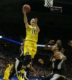 Michigan's Nik Stauskas scores against Wofford's Lee Skinner during second half action of their NCAA Tournament second round game Thursday, March 20, 2014 at BMO Harris Bradley Center in Milwaukee Wisconsin.