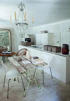 La cocina desemboca en el salón. Las piezas de ratán son de los años cuarenta. La mesa es una pieza restaurada por Morabito. Sillas de Arne Jacobsen y lámpara de Murano de los años cuarenta.