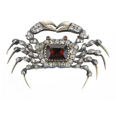 A cushion cut garnet is the body of this antique (late 19th century) crab brooch.
