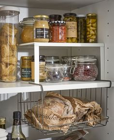 Storing food at home IKEA VARIERA white coated steel shelf insert and OBSERVATÖR metal clip-on basket are no-drill solutions that create more pantry shelving space for jams, jars, and bottles of different sizes.