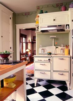 The Wedgewood gas stove features salt and pepper niches, burner covers, and a lamp. The dining room beyond has its original Douglas fir built-ins and wainscot. Kitchen Stove, Kitchen Reno, Kitchen Remodel, Kitchen Dining, Kitchen Cabinets, Dining Room, Kitchen Ideas, 1940s Home, Retro Home