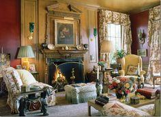 Mario Buatta via Cote de Texas . . light colored fabrics bounce off dark walls and honey pine fire place surround.