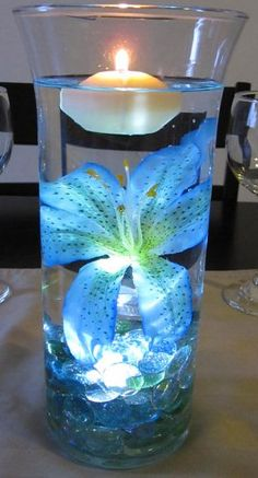 Center Piece....................     but maybe with clear marbles, dark blue lily, white orchid spray above it, topped with a navy blue floating candle.