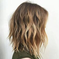 """The textured lob is the """"it"""" hairstyle of Spring 2017. Models were seen with these shoulder-length cuts with textured, thinned-out ends. This particular model is sporting sun-kissed highlights in this shoulder-length hairstyle."""
