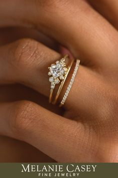 A unique engagement ring featuring a princess cut diamond focal accented by clusters of white diamonds. Available in 14k yellow, rose, or white gold, the Stargaze Ring can also be made with a natural or lab-grown diamond center. For more information, visit melaniecasey.com!