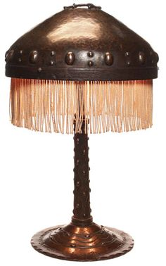 """Unusual Arts & Crafts lamp, hand hammered with tooled and raised designs and fringe to bottom of shade, good original patina, 12""""w x 20""""h"""