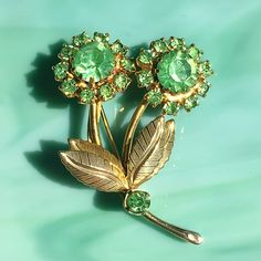 This charming peridot rhinestone vintage 1960s flower pin may be petite but its colorful blooms and bright gold-tone detailed leaves are so cheery. The chaton stones are prong-set with beautiful faceting. Its well-made and lightweight. This pretty pin is in fantastic vintage condition and would make the perfect summer jewelry gift for your favorite flower lover or gardener to wear on a lapel, scarf, purse, or hat. It can even be added to a hair tie as an eye-catching accessory. Check out…
