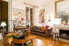 how is this room so warm with white walls?  is it the floors?  the gold?  i want i want i want!  The quintessential Parisian apartment