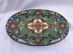 This cheese box is hand painted in the Hallingdal style of the beautiful folk art of Norway called Rosemaling. Rosemaling is a decorative folk art that began in the 1600s and is traditionally done on painted wood. This lovely oval box is 15 x 9 x 3 in size. This box is base coated