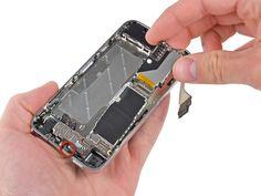 20. Retire con cuidado la placa lógica del iPhone, pensando en los cables que pueden quedar atrapados. Tenga cuidado de no dañar la pequeña pestaña dorada (marcada en rojo, en la parte superior), ya que es muy frágil.