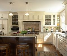 The walnut island was glazed to add dimension and the enameled cabinets were also glazed. A mix of oil rubbed bronze hardware and antiqued nickel complete the look of ageless design.