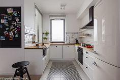 Biała wąska kuchnia została zaaranżowana w skandynawskim stylu. Białe szafki i ściany kontrastowo zestawiono z drobnymi...