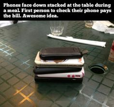 Phones face down stacked at the table during a meal. First person to check their phone pays the bill.