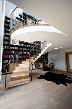 Spiral Staircase Effortlessly Flows by Floor-to-Ceiling Bookcase - My Modern Met