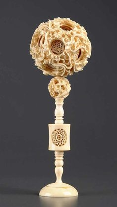 An ivory puzzle ball, comprising ten balls, the outer ball carved with dragons amongst ruyi clouds; together with a part stand which includes a ball comprising of four balls