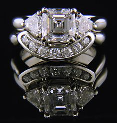 An Asscher-cut diamond set with two calf-head diamonds in a hand-crafted platinum ring @}-,-;--