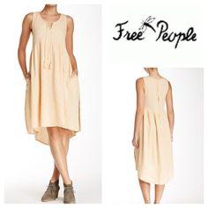"Free People Hi-Low Dress Tassel strings accent the split neck of a hi-lo sundress with a long keyhole and empire waist. - Split neck  - Sleeveless - Back keyhole - 2 on-seam slash pockets - Hi-lo hem - Unlined - Approx. 40"" shortest length, 46"" longest length, pit to pit 20-1/2"" - Color:  Light Peach Fiber Content: 100% cotton Free People Dresses"